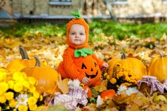 Child in pumpkin suit on background of autumn leaves