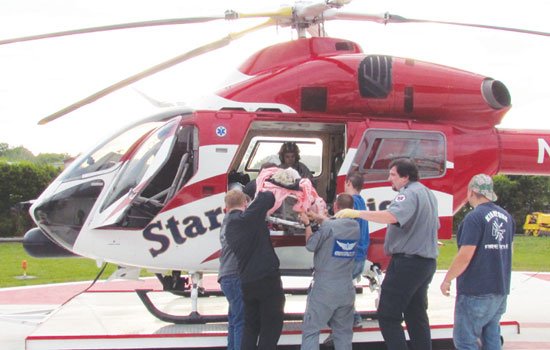 Starflight crew and EMS loading an accident patient aboard the helicopter.
