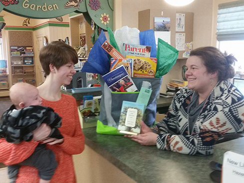 Lego Club volunteer, Jessie Anderson and her son Ben, investigate a Big Read Prizebag that adults can win by entering a new reading contest.