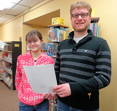 Leah Rexford, volunteer, and Mike Magnuson, library associate, look over the registration form for the 10th anniversary Cummins Run for Literacy that will take place May 7.