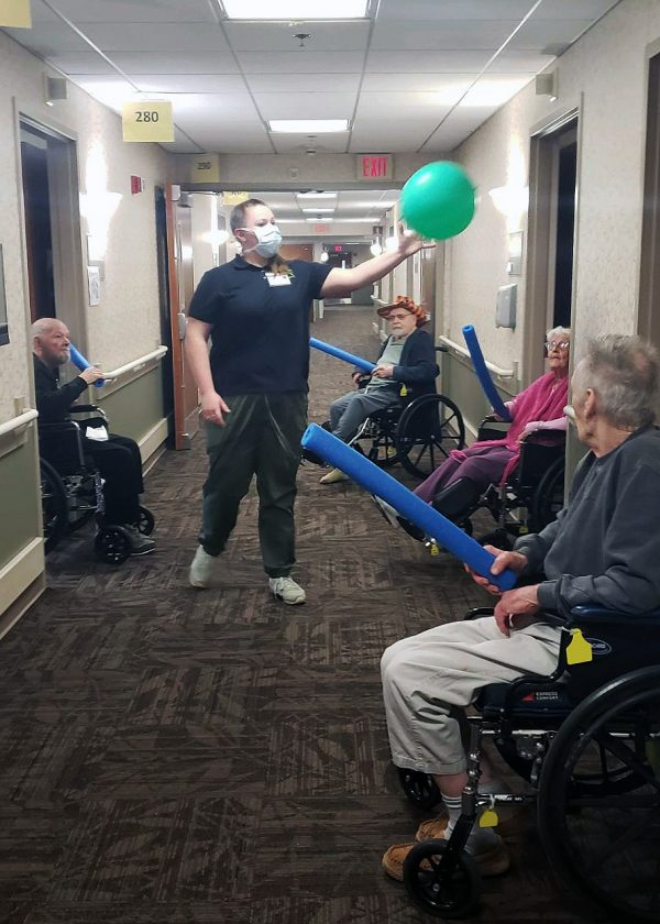 Residents from the Lutheran Home and Rehabilitation Center play Pool Noodle Baseball in the hallway with an LHRC Unit Tech. This activity and others provide entertainment and exercise to the residents while maintaining a safe social distance.