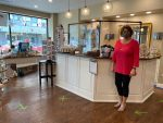 Owner Michelle McCray stands by the check out in the Dot's Gift Boutique. Please note the shield, signage and arrows and X for traffic control.