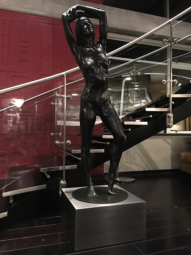 Black bronze nude sculpture of a ballet dancer on a square stainless steel base