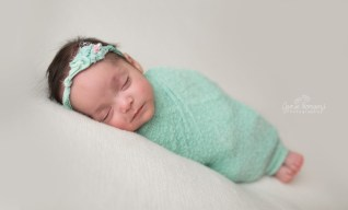 Micro preemie, newborn twin session. Baby wrapped in mint on white backdrop with mint and pink headband.