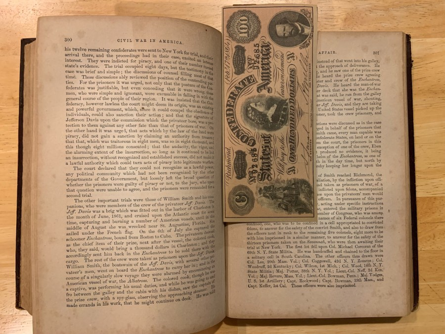 an open copy of THE CIVIL WAR IN AMERICA, Vol I with a crisp $100 Confederate note stuck in as a bookmark