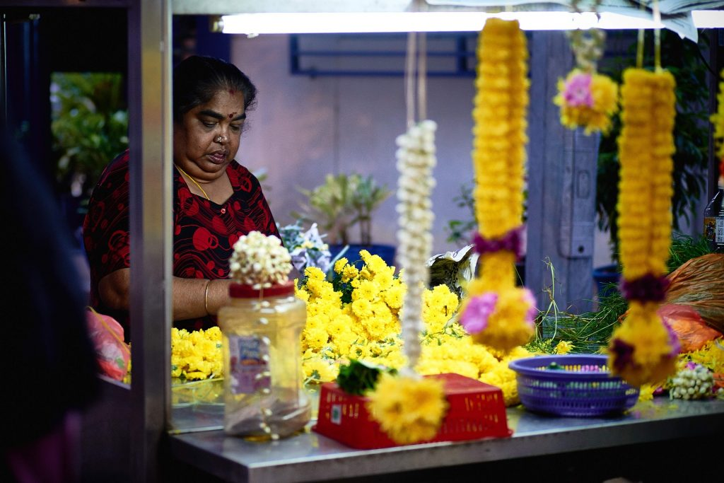 A picture of a woman at a flower stall in Asia, s small business that has a place in a larger order. Starting out with a small idea.