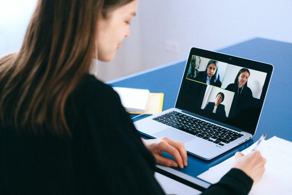 woman on a zoom call, discussing things with teammates, learning from others in business