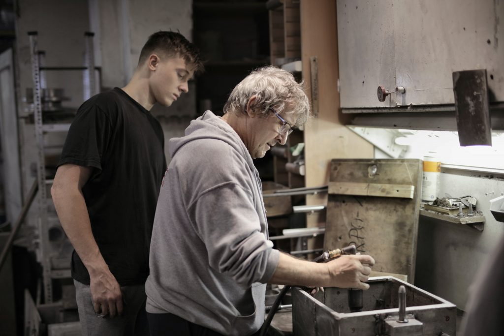 two men together in a work shop - young man serving an apprenticeship in an effort to learn more about the area he wants to move into in business