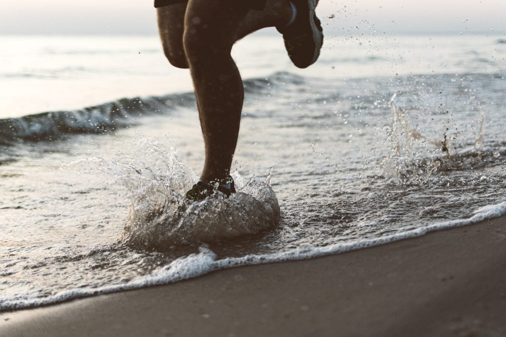 image of a pair of feet in runner running through the water of a beach shore