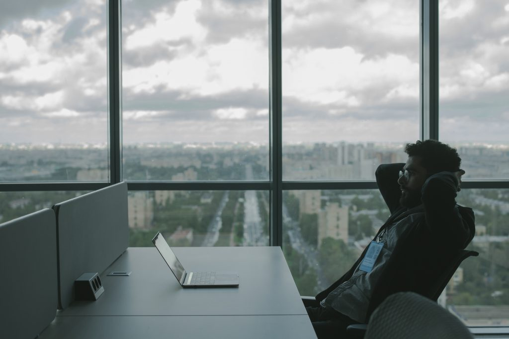 picture of a man sitting at a desk with a background of a city behind him through the window