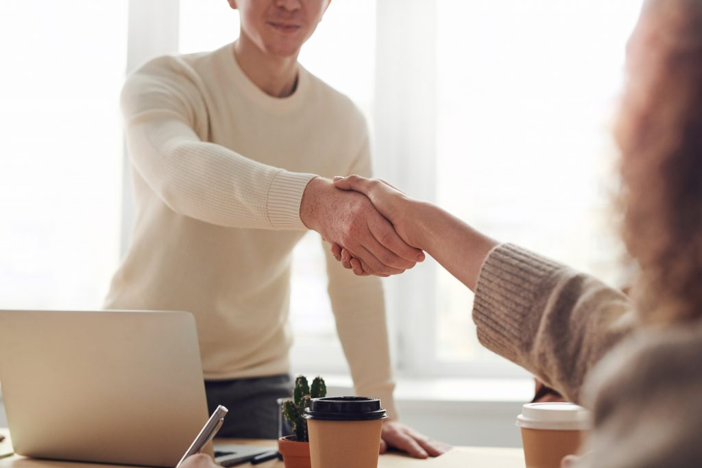 two business people shaking hands, representing a successful meeting about pay