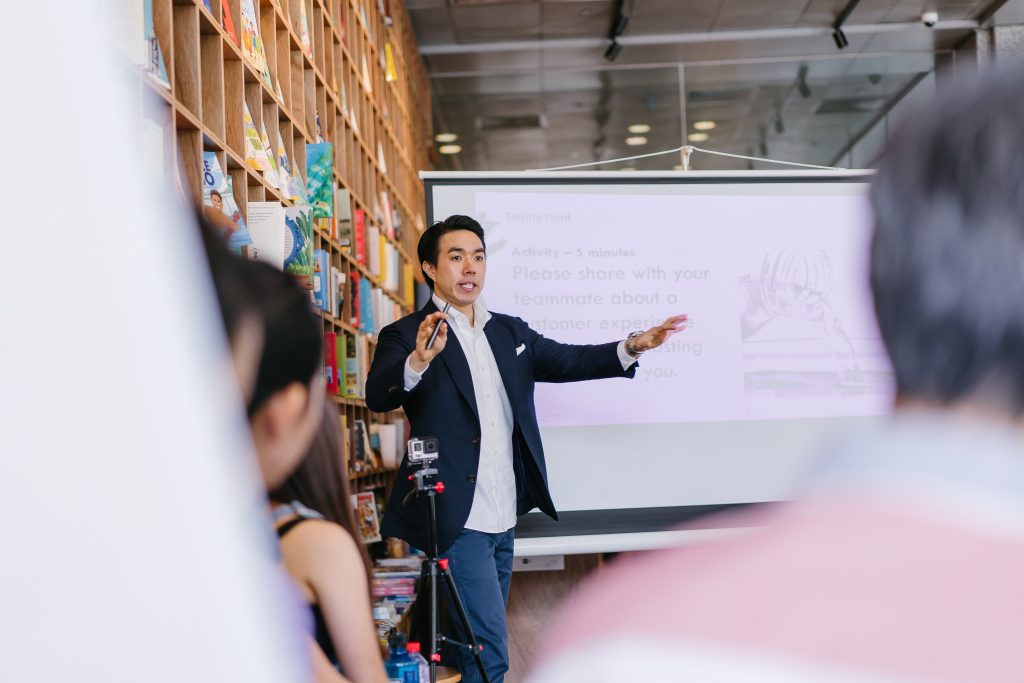 man in business suit - entrepreneur - delegating at a team meeting. with whiteboard in background