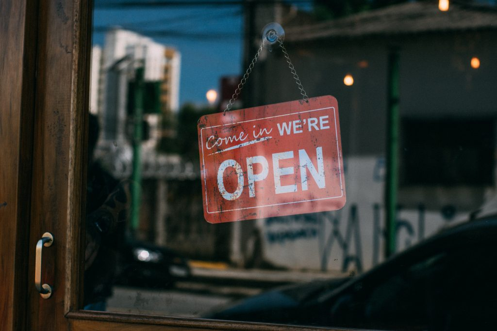 """image of a shop front saying """"come in we're open"""" - business owner, example of an entrepreneurial pursuit"""