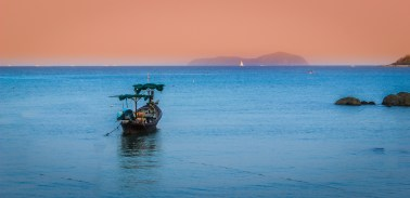 A solitary boat rests on a calm evening in Rawai Bay, Phuket