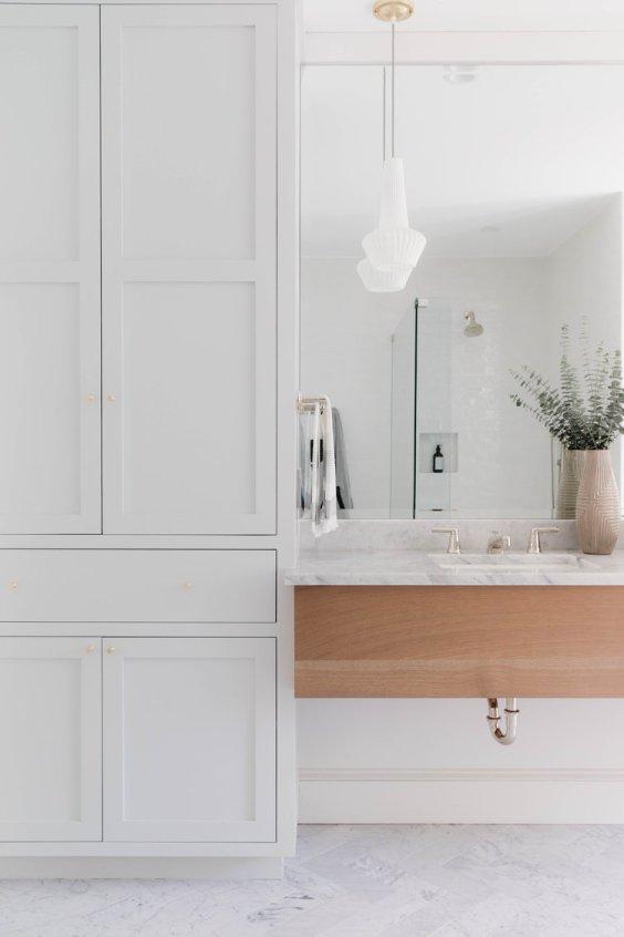 Beautiful modern bathroom design with soft gray green cabinets and light wood vanity - Rehabitat Interiors