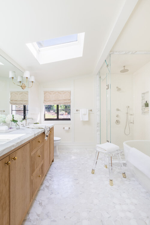Classic white bathroom design with light wood vanity cabinets, glass shower enclosure, and brass sconces on mirror - Taylor Anne - bathroom ideas - bathroom decor