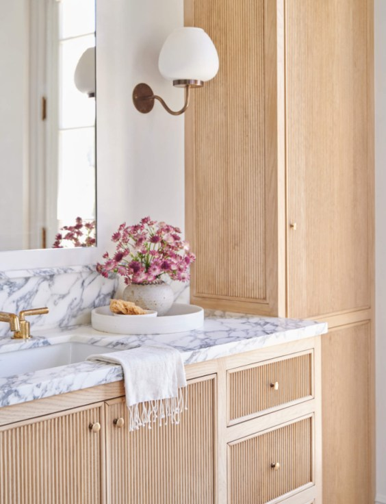 Beautiful bathroom with light wood vanity and cabinets, marble countertops and white and brass sconces - bathroom remodel - bathroom ideas - bathroom decor - Amber Interiors - Tessa Neustadt