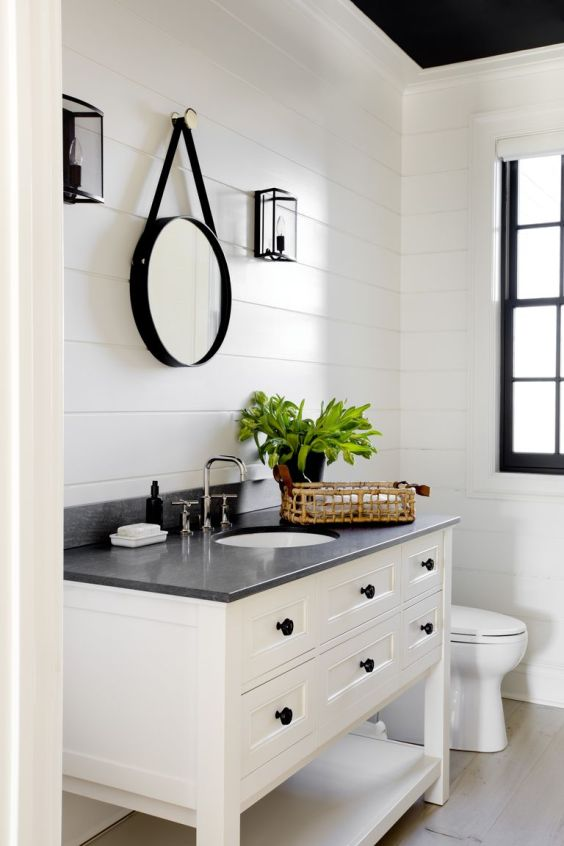 Beautiful powder bathroom with white vanity and black countertop