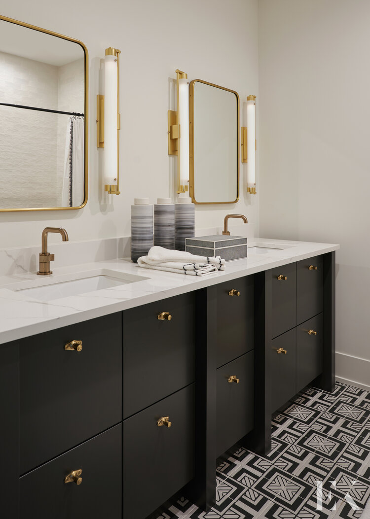 I love this beautiful modern bathroom with double sinks, dark blue-black vanities and brass faucets, pulls, mirrors and sconces - Elizabeth Krueger Design
