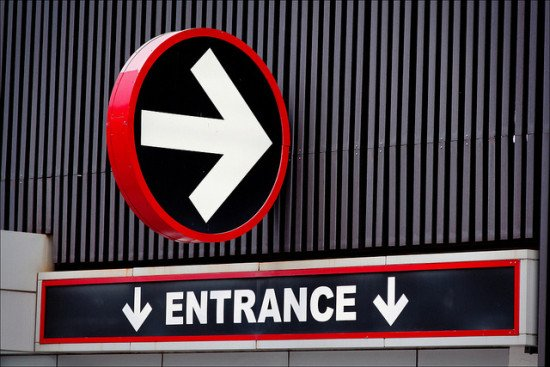 """A sign reading """"Entrance"""" and pointing downward."""