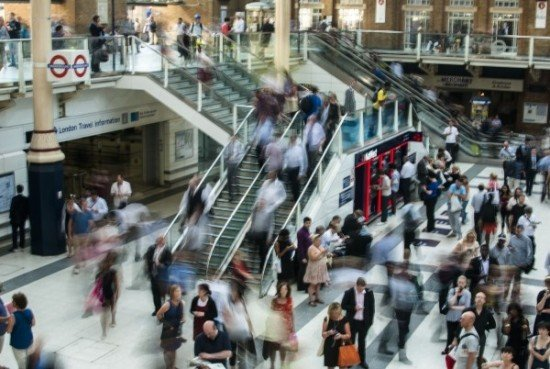 A time-lapse photo of people milling about an interior with stairs and an escalator.
