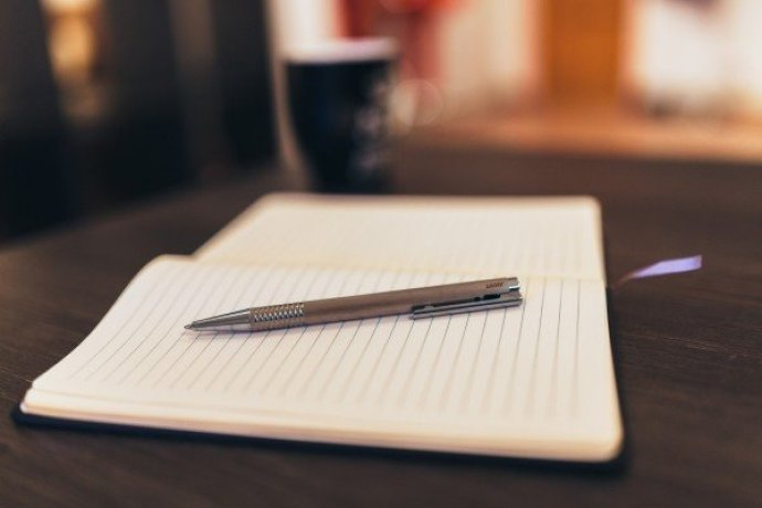 A pen resting on a blank journal page.