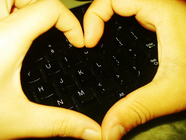 Hands forming a heart symbol over a keyboard