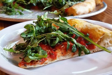 vegan pizza with red sauce and arugula