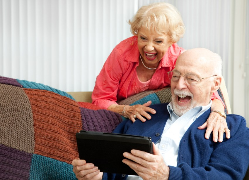 Grandparents Laughing with Tablet