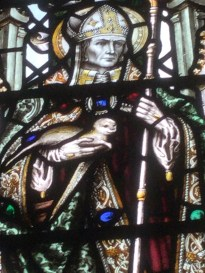 Detail of stained glass window depicting Saint Cuthbert holding an otter.