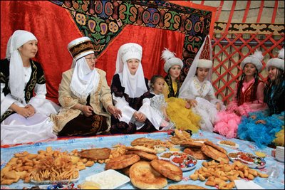 During my Peace Corps service, I was involved with the women in northern Kyrgyzstan.  Here is an image taken from Google Images that remind me of the women that I knew: taken inside a Kyrgyz yurt (nomadic tent),  the women are dressed in traditional costumes (currently used for celebrations) and are serving the traditional kinds of bread on a tablecloth placed on the ground (method still used for large groups of people)