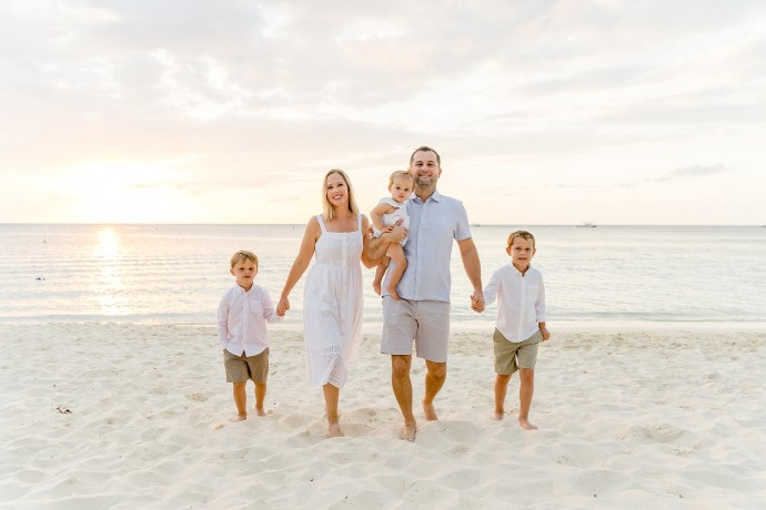 family walking holding hands on beach