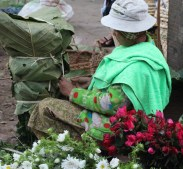 This woman is wrapping flowers in banana leaves.