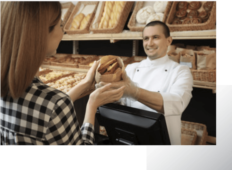 Msn selling a loaf of artisan bread to a woman