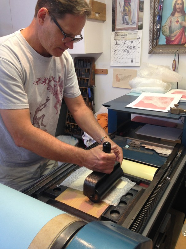 Brent Bond using a roller to off-set print the 3rd color