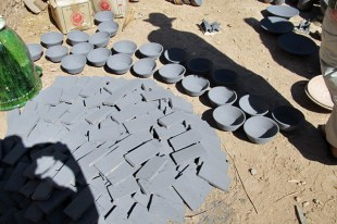 Raw glazed tiles and bowls ready for the kiln.