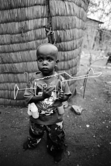Afar boy with hand-made toy Kalashnikov and ammunition belt with grenades made from recycled materials. Gewane, Afar region, Ethiopia