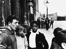 Two groups of men and boys on Southam Street, North Kensington, London. A young West Indian boy looks straight at the camera. 1959