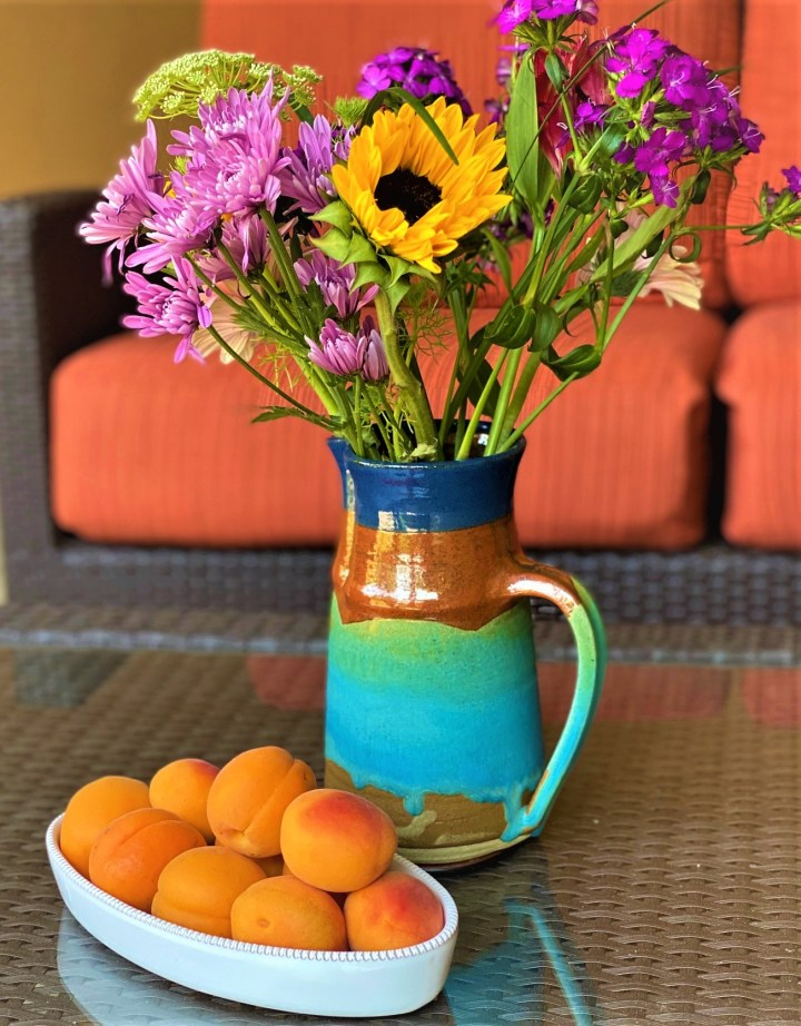 A dish of ripe apricots with a colorful pitcher of summer flowers