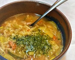 A bowl of Minestrone di Verdure, an Italian soup topped with pesto