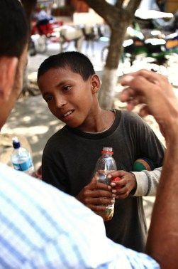 Allan shows this young boy a magic trick. He's high from the shoe glue at the bottom of the bottle in his hand. For just 5 córdobas, the children of the street sniff away their troubles.