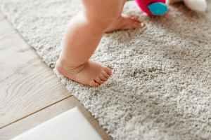 baby s standing on gray floor rug