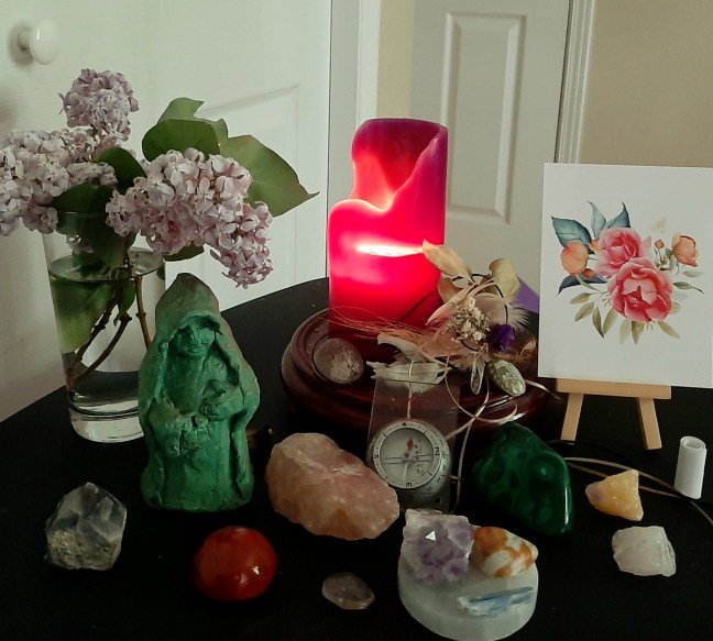 My morning altar includes a bouquet of lilacs, my father's compass, and a crone modeled in artists' clay by my father many years ago.