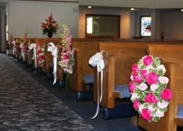 ceremony flowers, pew decorations, pink, wedding flowers, wreath, white bow, lake of the ozarks, weddings, osage beach, lake ozark, camdenton, janine's flowers