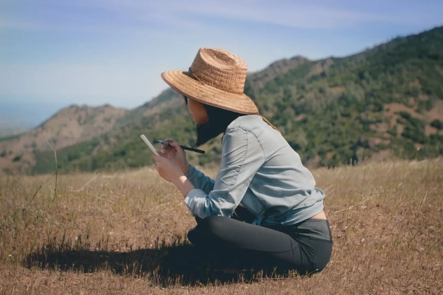 woman writing in a field