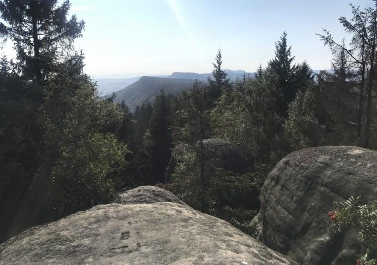 Supi Hnizgo, Sępie Gniazdo (702 m) i widok na krawędź Broumowskich z Koruną, Božanovskym Špičakem i oboma naszymi Szcelińcami tam najdalej, hen.
