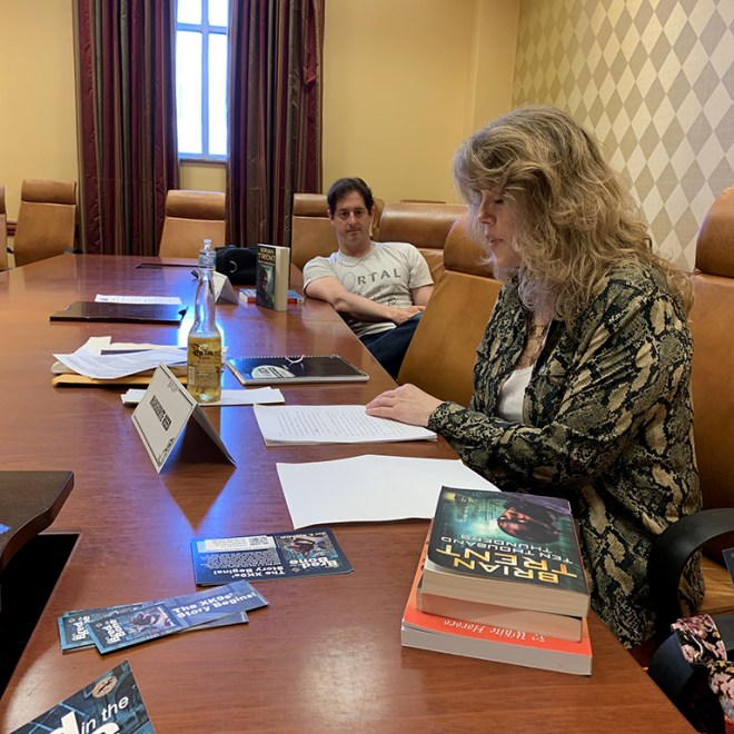 Marguerite Reed shares an excerpt from a new short story at her reading. Fellow author Brian Trent listens in the background.