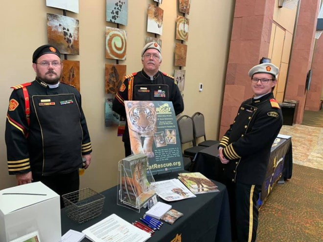 Here's a photo of a table manned by three uniformed members of The Royal Manticoran Navy. On the table is a display in support of their charity, Big Cat Rescue of Tampa, FL.