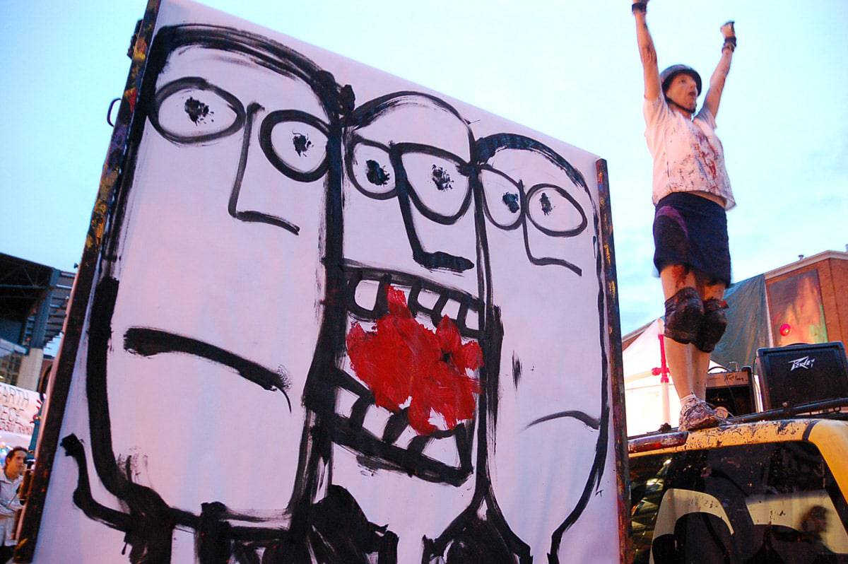 performance artist wearing helmet and kneepads stands on truck next to large painting of faces done in a modern primitive style by Julie JAO
