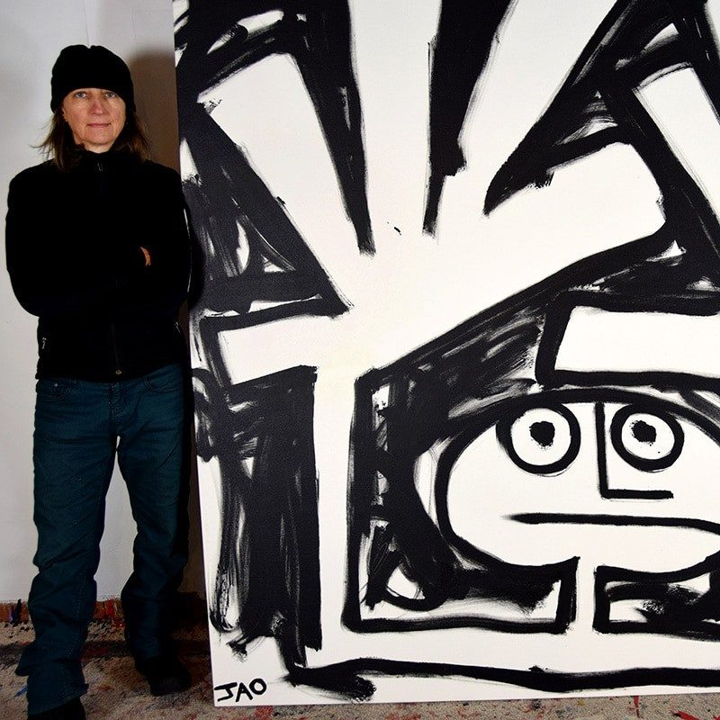 JAO the artist wearing black cap standing next to 8 foot square black and white figure painting with large abstract hands
